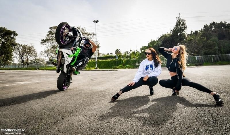 אופנוע על גלגל אחד, שתי נשים, מגרש אספלט, עצים, smirnov production לוגו
