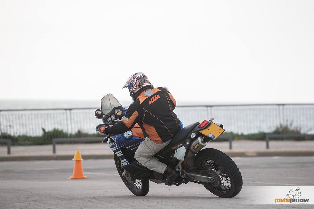 תמונה מאחור של אופנוע כחול בהטיה עם זנב בצד על מגרש חניה עם קונוס ליד הים, לוגו אופנוען מאומן