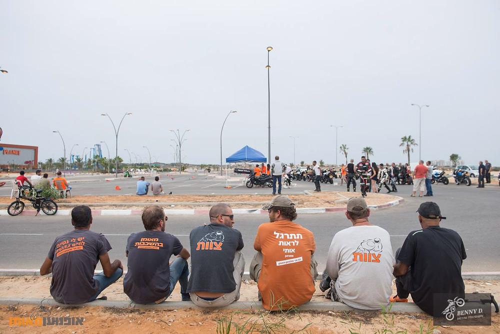 אנשים יושבים על שפת מדרכה במגרש חניה