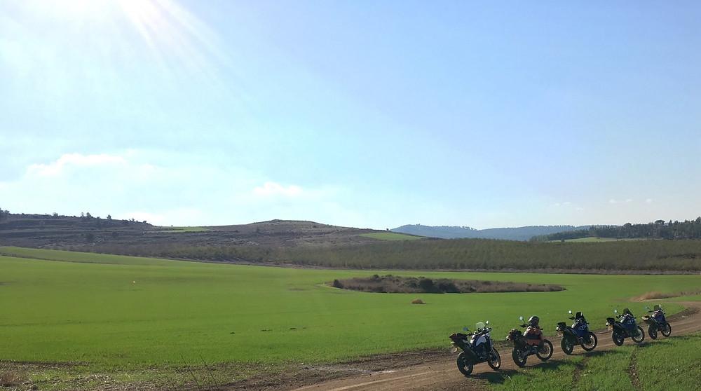 חמישה אופנועים עומדים בצד שביל ברקע של שדות ירוקים וגבעות עד האופק