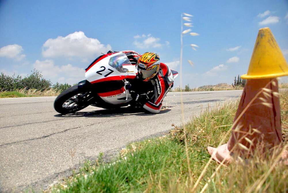 אופנוע מירוץ מספר 27 בהשכבה עם מרפק וברך באספלא על אספלט סדוק, קונוס בצד על הדשא