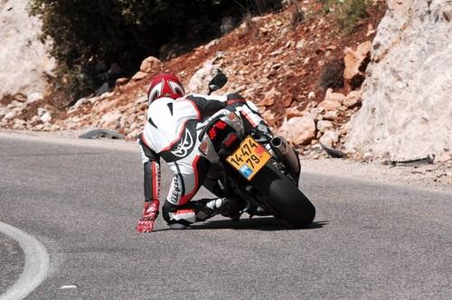 תמונה מאחור של אופנוע בפניה בכביש על רקע סלע, רוכב עם ברך ויד על האספלט.