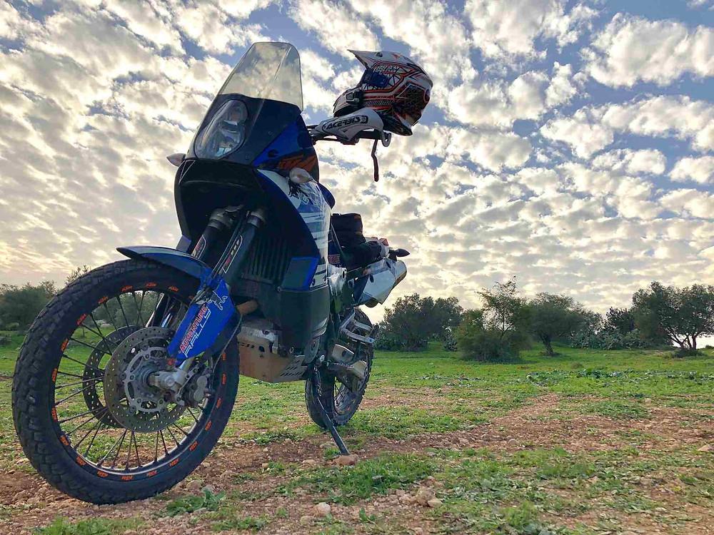 קטמ אדוונצ'ר 950 כחול עומד על ג'ק צד בשטח עם קסדה תלויה על המראב, רקע ענני כבשה מוארים מהשמש