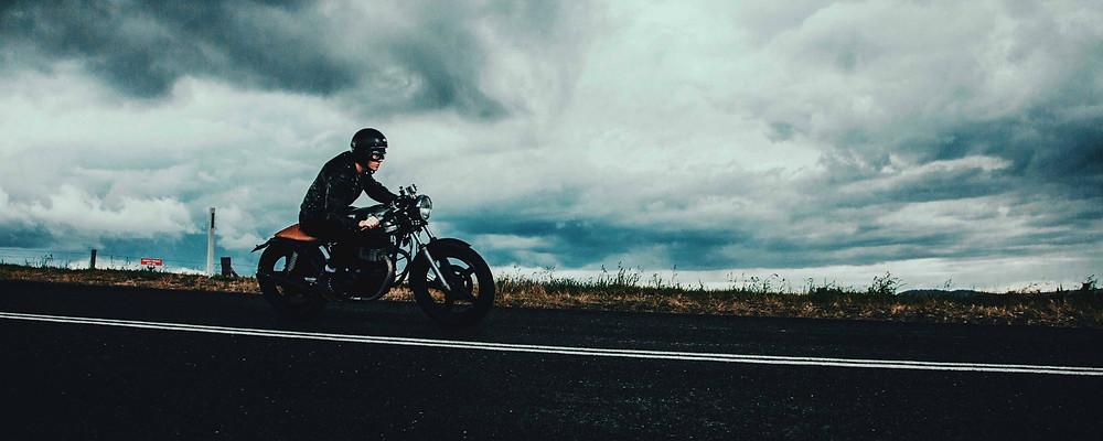 אופנוע עתיק נוסע על כביש, שמיים עם עננים ברקע