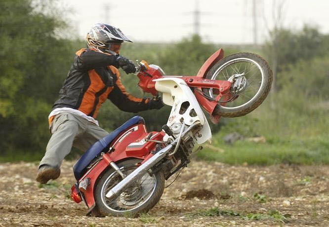 הונדה קאב בווילי על אדמה, רוכב עם רגל באוויר רקע עצים