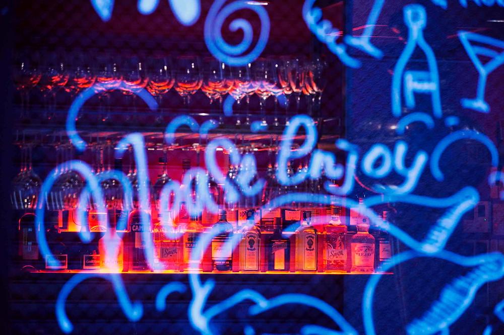 """כיתוב בכחול """"please enjuy"""" על זכוכית שמאחורי בר מואר באדום"""