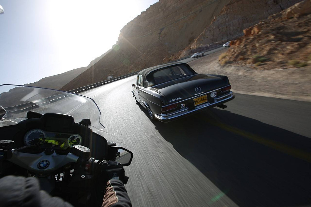 מבט מזווית ראיה של אופנוע על פניה בין הרים מדבר, מכונית מרצדס ישנה קצת לפני האופנוע.
