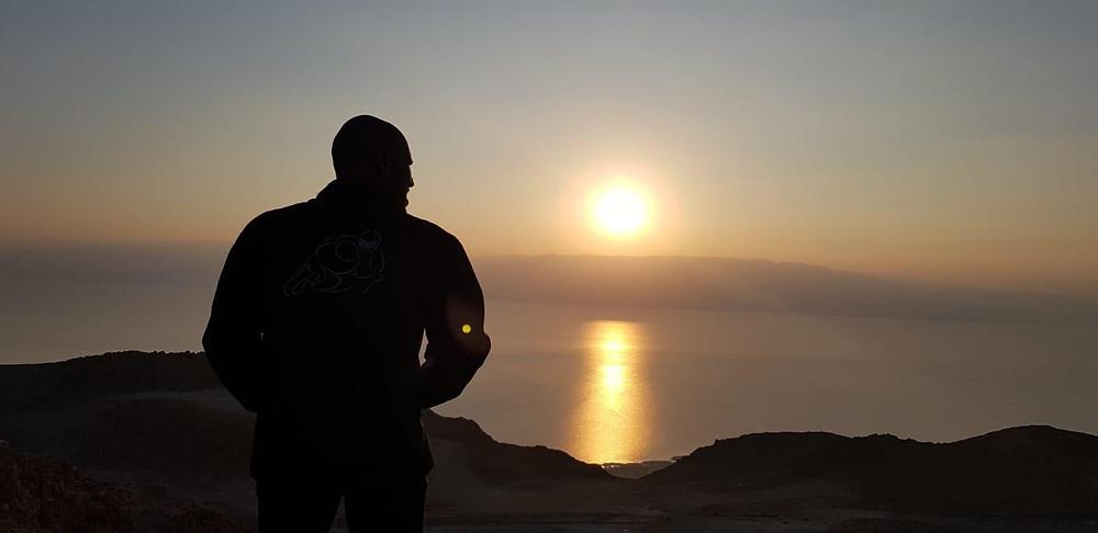 צללית של אדם  מביט על זריחה שמאירה על ים הרקע הרים