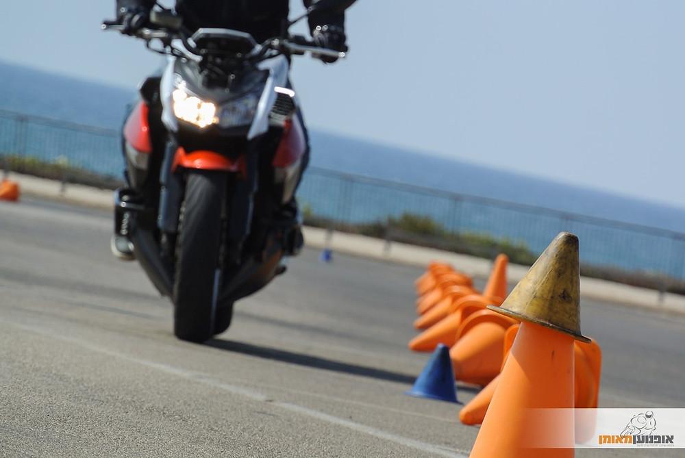 אופנוע פרונטלי לא בפוקוס, אספלט, מגרש רכיבה, קונוסים, רקע ים