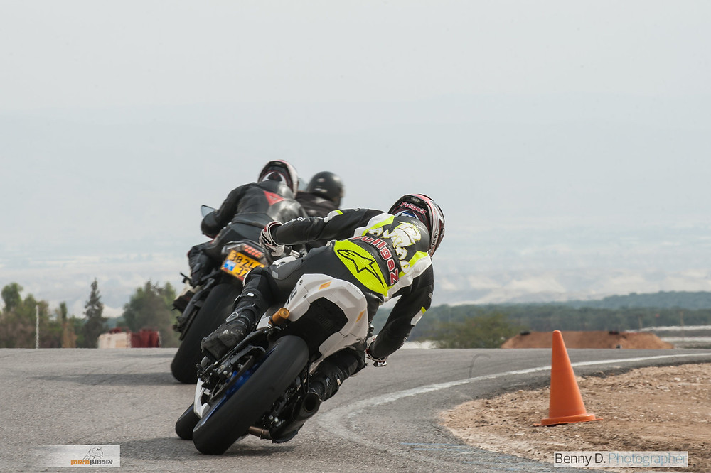 שלושה אופנועים אחד מאחורי השני בפניה ימנית מסביב לקונוס במסלול, רקע שמים אפורים
