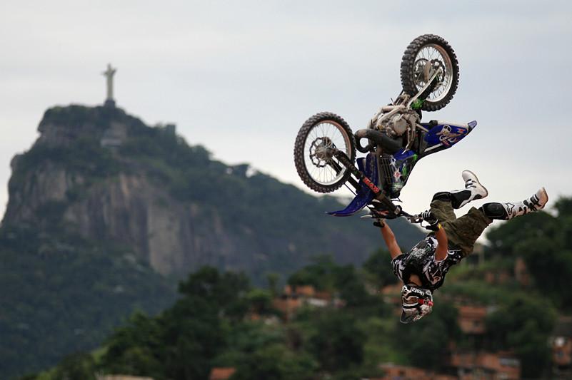 אופנוע הפוך באוויר במהלך תריל פריסטייל מוטוקרוס) ברקע הר עם מגדל בפסגה