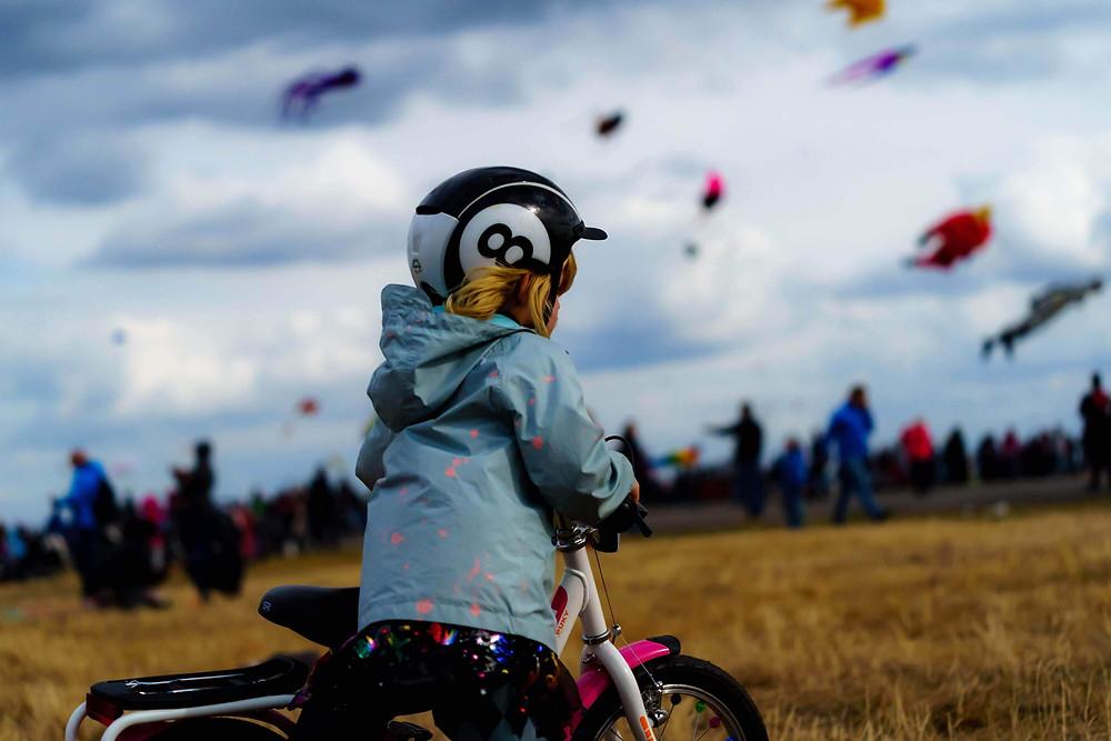 ילדה עם אופניים ורודות, קסדה עם מספר שמונה, עפיפונים בשמים, שדה מלא אנשים