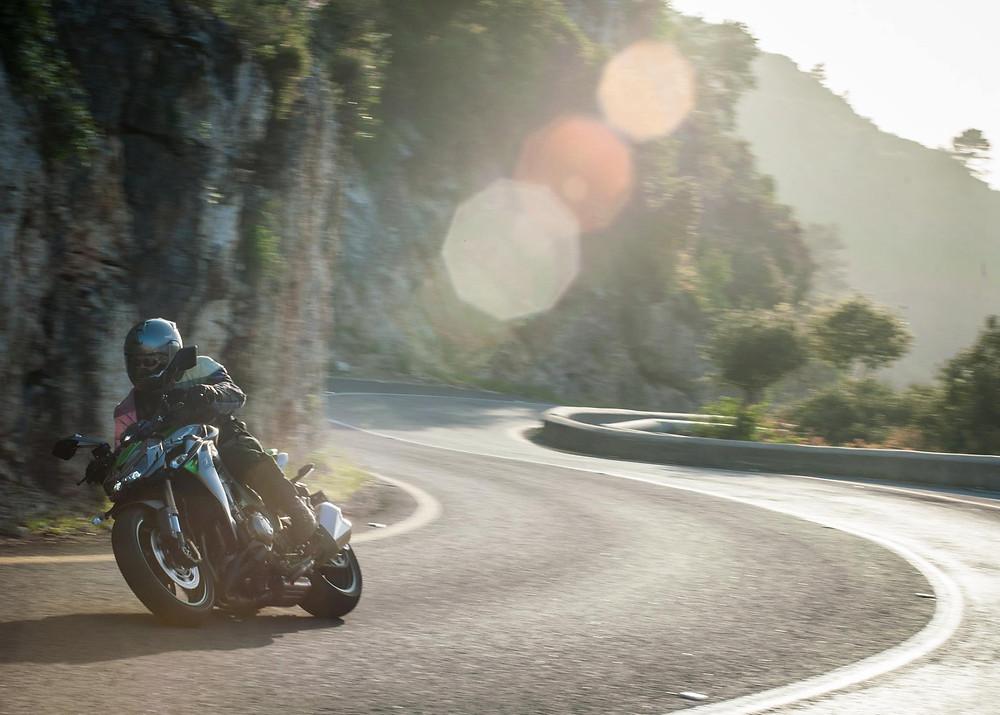 אופנוע נייקד בכביש הררי מפותל, קוואסקי Z800, סינוור שמש על העדשה