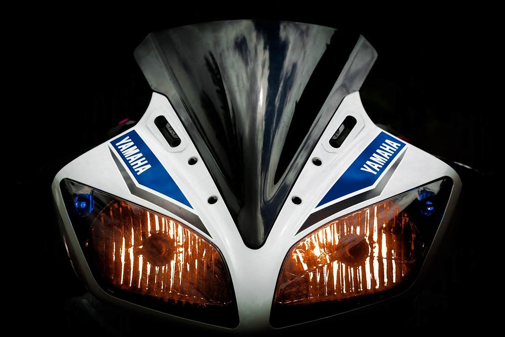 תמונת סטודיו עם רקע שחור של פנסים וחזית של אופנוע ימאהה לבן עם עיטורים כחולים