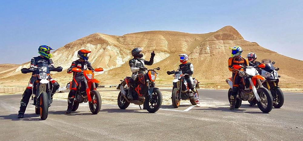 חבורת אופנועי סופרמוטו על אספלט ברקע הר חום