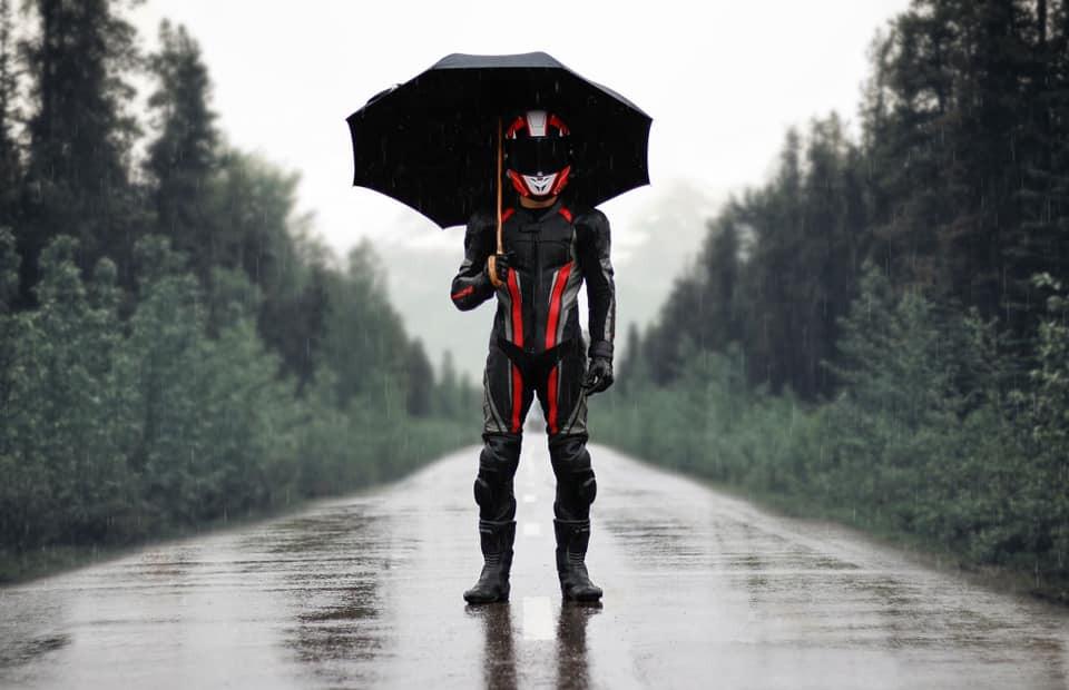 רוכב אופנוע עם חליפת עור וקסדה עומד בגשם עם מטריה על כביש רטוב בין עצים
