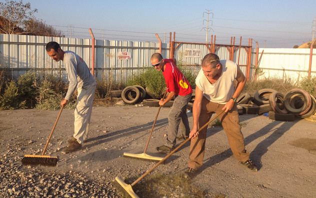 שלושה אנשים עם מטאטאים מנקים את האספלט מאבנים, רקע גדר עם חוט תייל