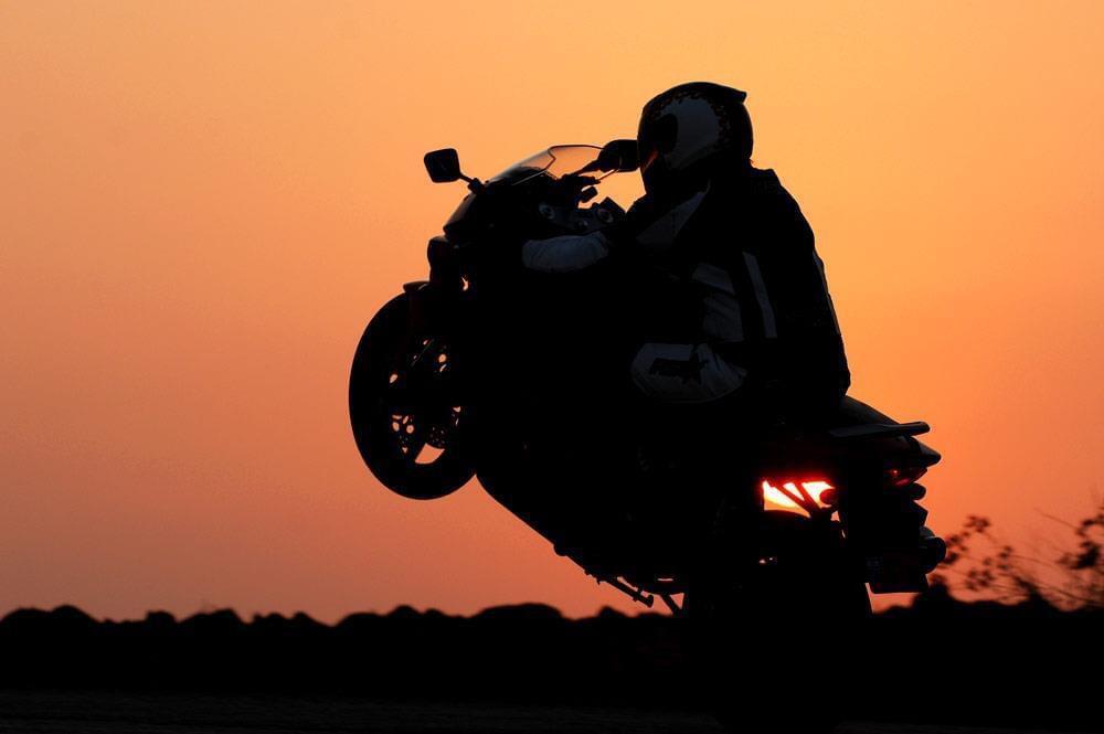 צללית של אופנוע בווילי ברקע כתום של שקיעה