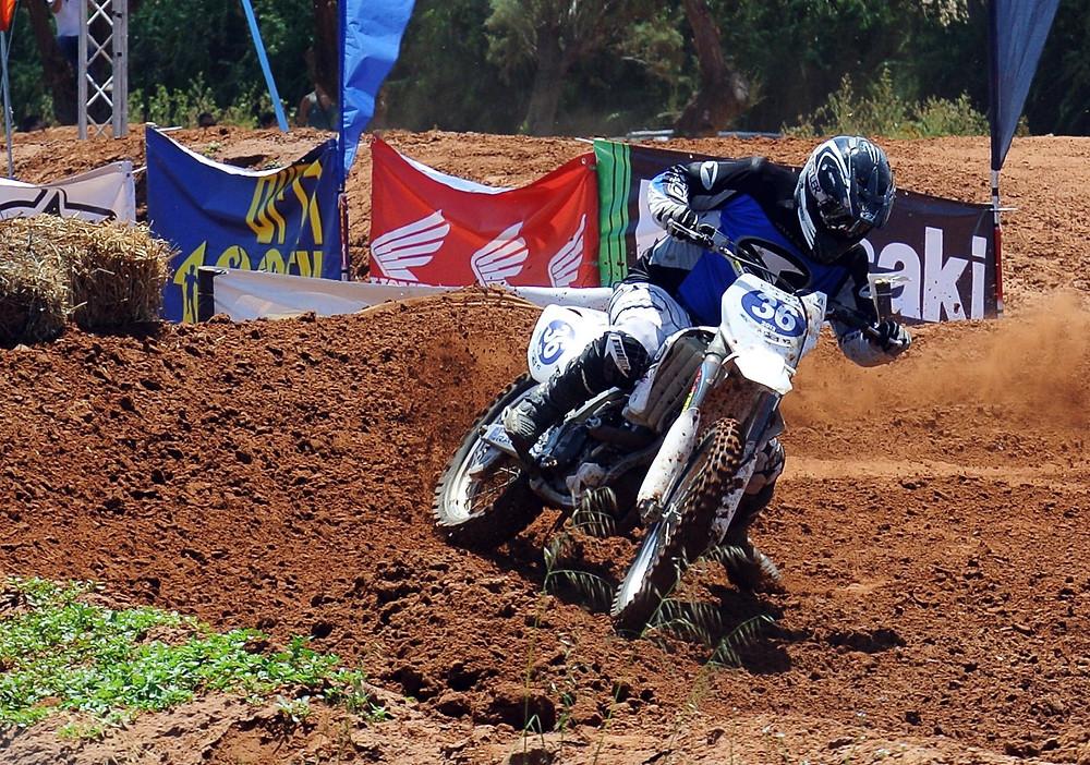 אופנוע מוטוקרוס לבן מספר 36 בפניה על הגז באדמה חומה