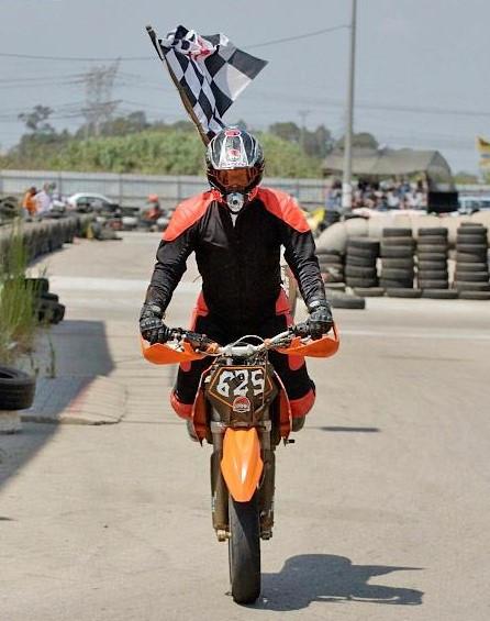 אופנוע KTM עם לוחית 625 בסטופי מול המצלמה, דגל שחמט מאחור