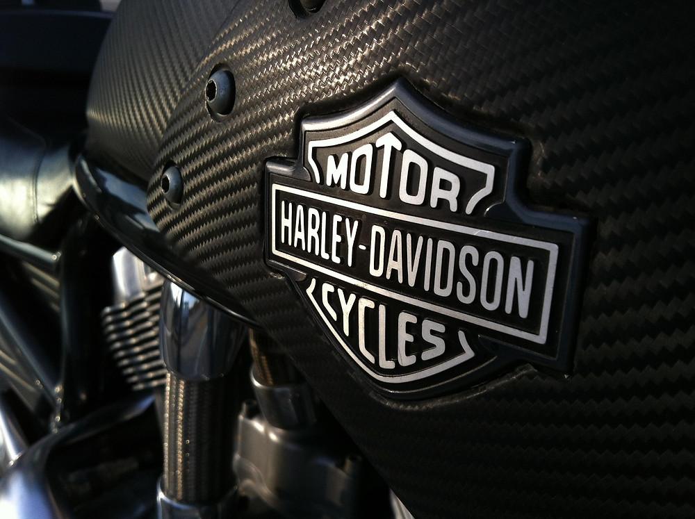 סמל של הארלי-דווידסון על מיכל דלק קרבון מנוע ברקע