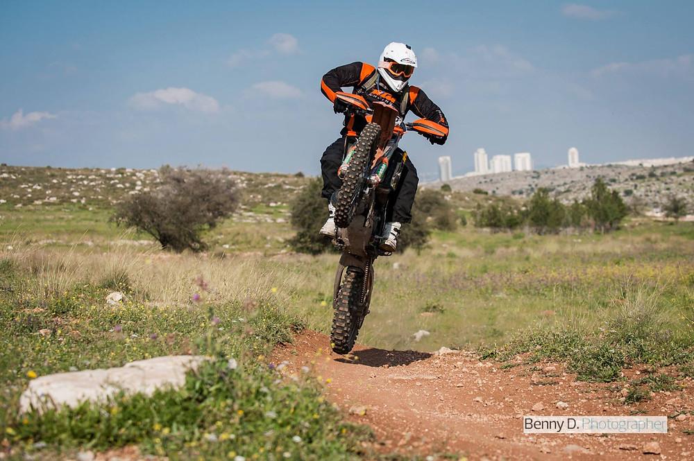אופנוע מניף גלגל קדמי לגובה תוך כדי קפיצה בשטח מסולע, גבעות וביניינים ברקע