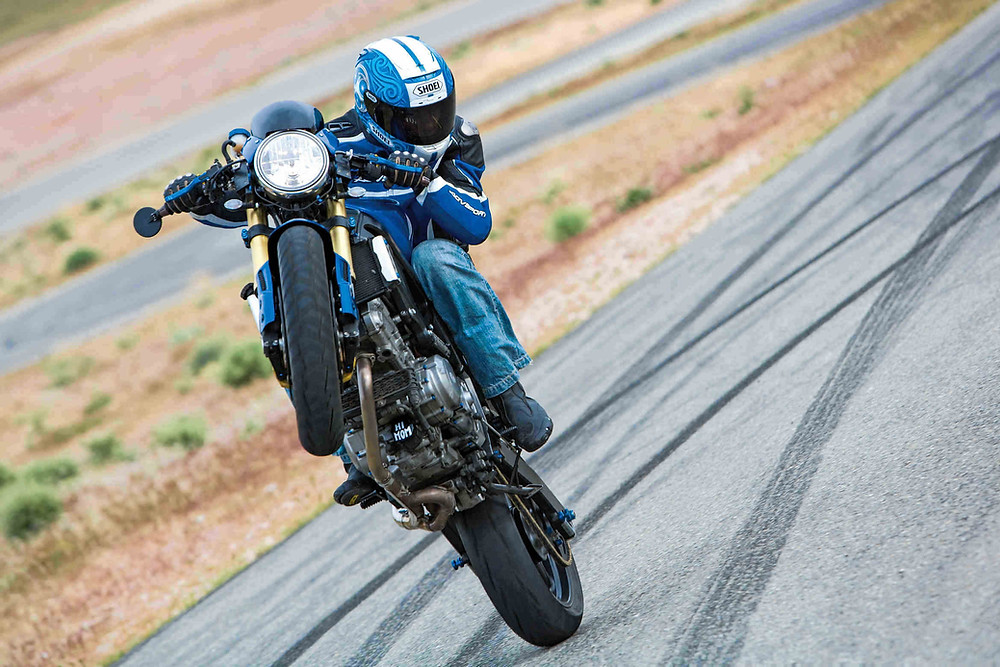 אופנוע כחול על גלגל אחד, רוכב מביט הצידה, רקע אדמה ואספלט עם סימני צמיגים