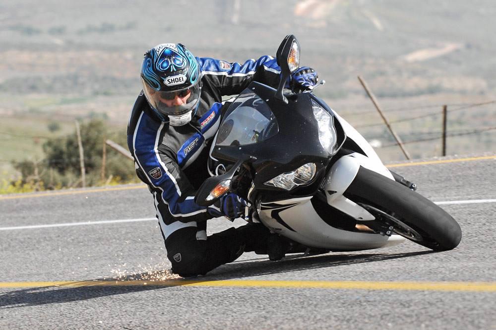 אופנוע ספורט בצבע שחור לבן בהשכבה בכביש, רוכב משייף ברך ומוציא ניצוצות, ברקע גדר תיל ושדות
