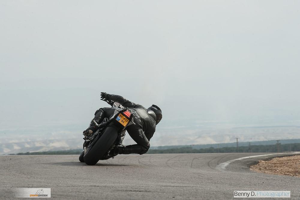 אופנוע מאחור בהטיה על אספלט, גוף הרוכב צולל פנימה לכיוון הפניה