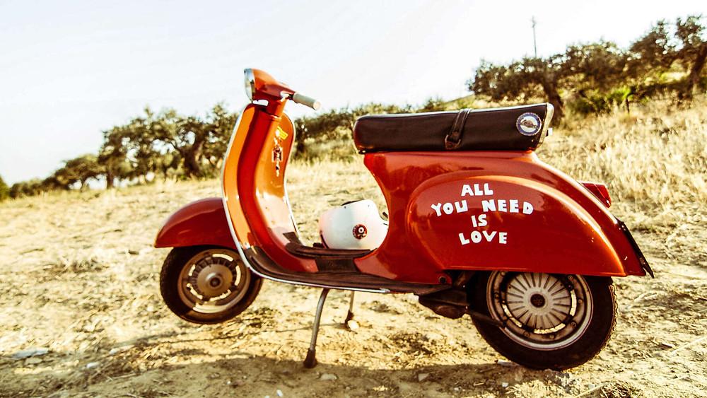 וספה אדומה חונה על עפר, קסדה לבנה, כיתוב: all you need is love על הוספה