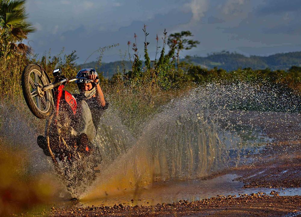 אופנוע על גלגל אחד, מים ניתזים משלולית, עצים