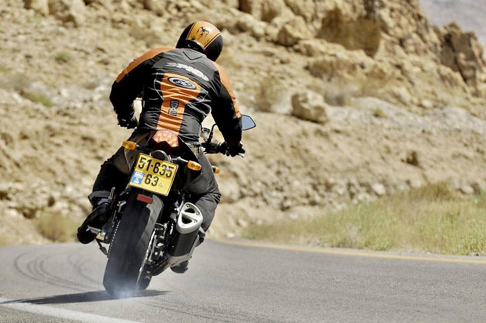 אופנוע מאחור, נועל ומעלה עשן מהגלגל האחורי בבלימה על כביש, רקע הר חום וסלעים