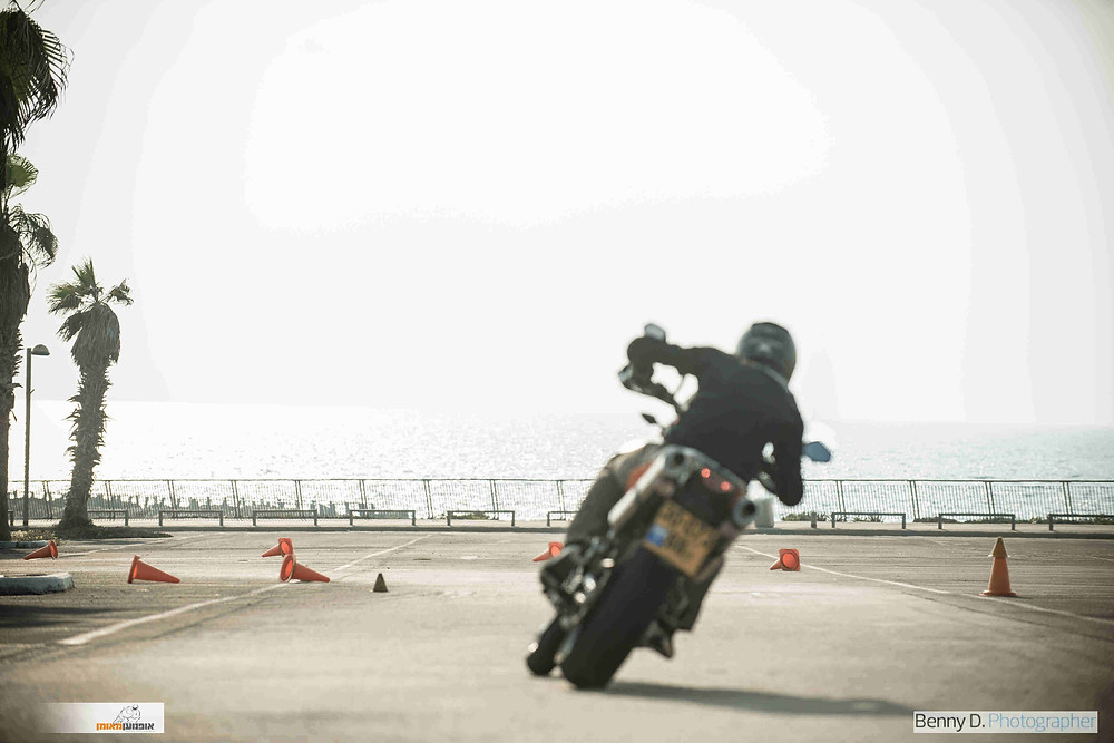 אופנוע נוסע הלאה לעבר הים על מרגש עם קונוסים מפוזרים ודקלים