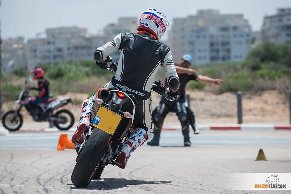 מבט מאחוןר על אופנוע משכיב ימינה, ברקע מדריך רכיבה מראה את הדרך