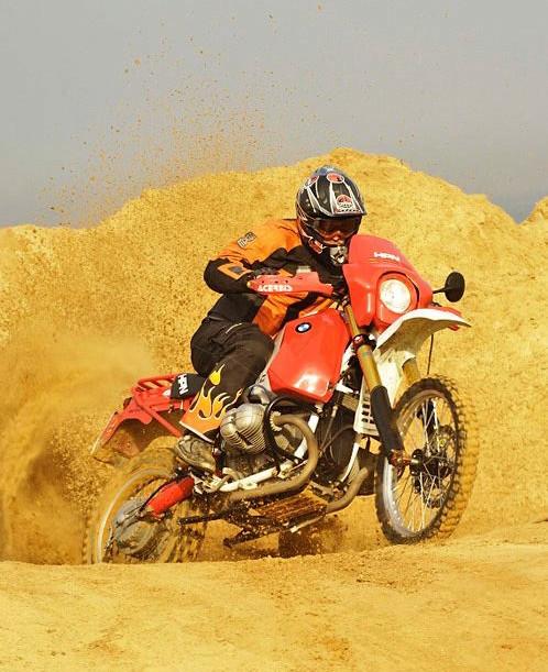 אופנוע במוו R1150GS בשטח. רקע הרי חול ורסס אדמה שעף מהגלגל האחורי