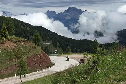 אופנוע על כביש מפותל, נוף הרים, עננות