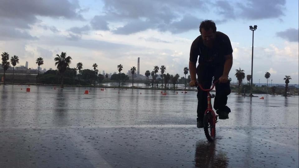 אדם רוכב על אופניים בגשם במגרש חניה רטוב עם קונוסים מפוזרים.
