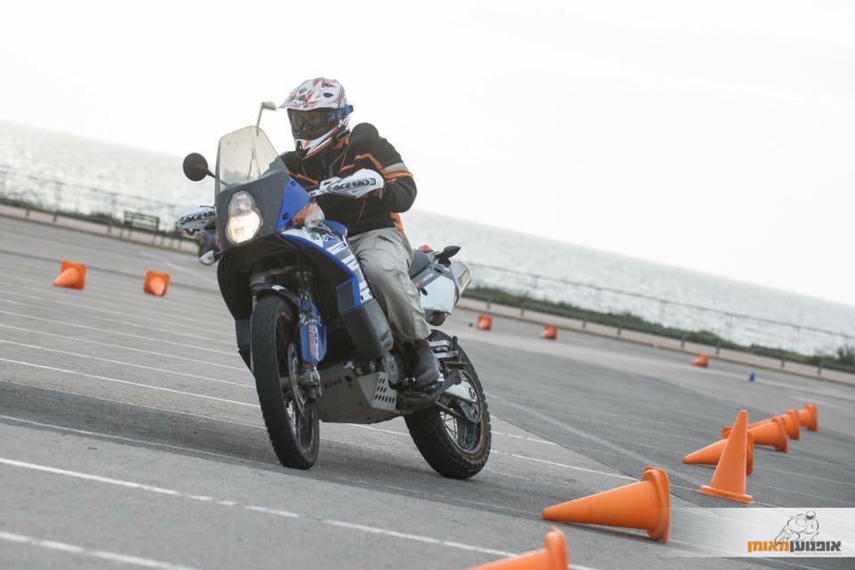 קטמ אדוונצ'ר 950 כחול בכניסה בהחלקה לפניה במגרש עם קונוסים, אופנוען מאומן