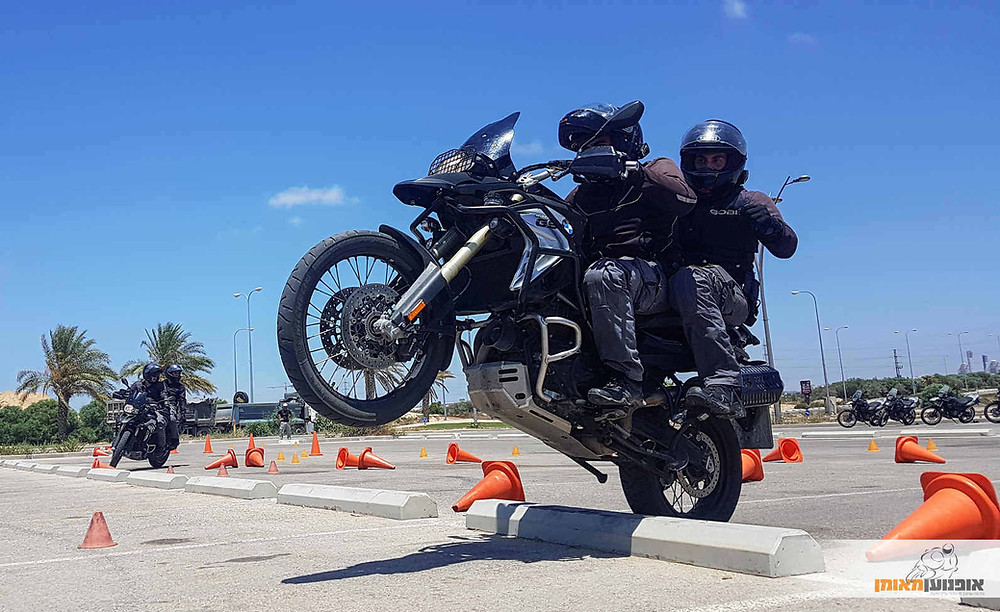 תרגיל מסכם במגרש, קורס רכיבה מבצעית אופנוען מאומן. אופנועי במוו משטרתיים בהרכבה, אחד עובר מדרכה בווילי וברקע עוד זוג בתמרון בין קונוסים.