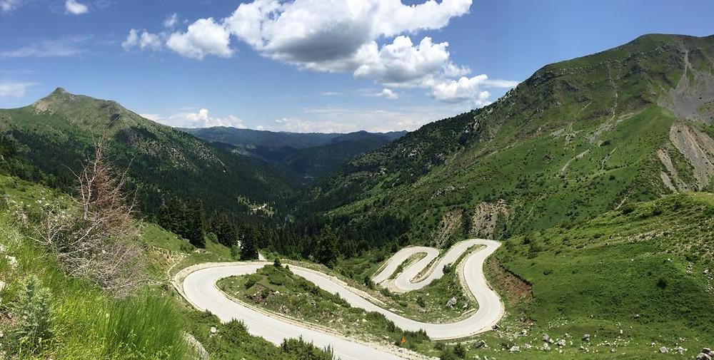 כביש מתפתל הלאה ונעלם מטה אל הרים ירוקים ברקע שמיים כחולים עם ענן לבן