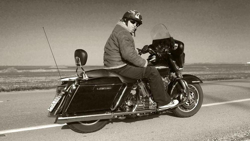 אופנוען עם קסדת חצי על אופנוע קאסטום