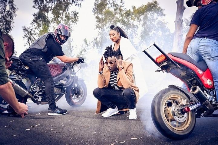 התרחשות במגקש חניה, שני אופנועי סטאנט, שני אנשים במרכז מסתכלים למצלמה, עצים