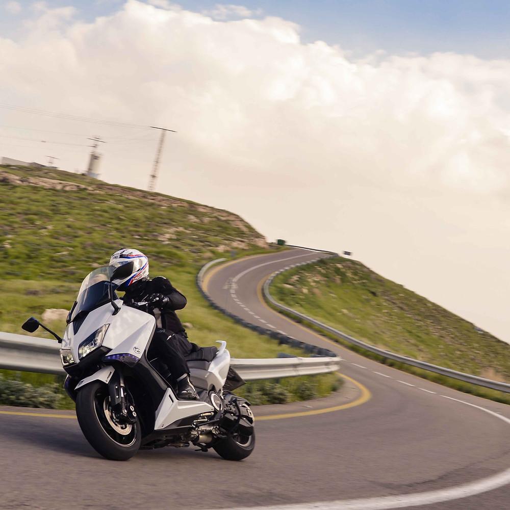 קטנוע טימקס לבן בהטיה בכבישמפותל במורד מגבעה ירוקה, ענן לבן גדול ברקע