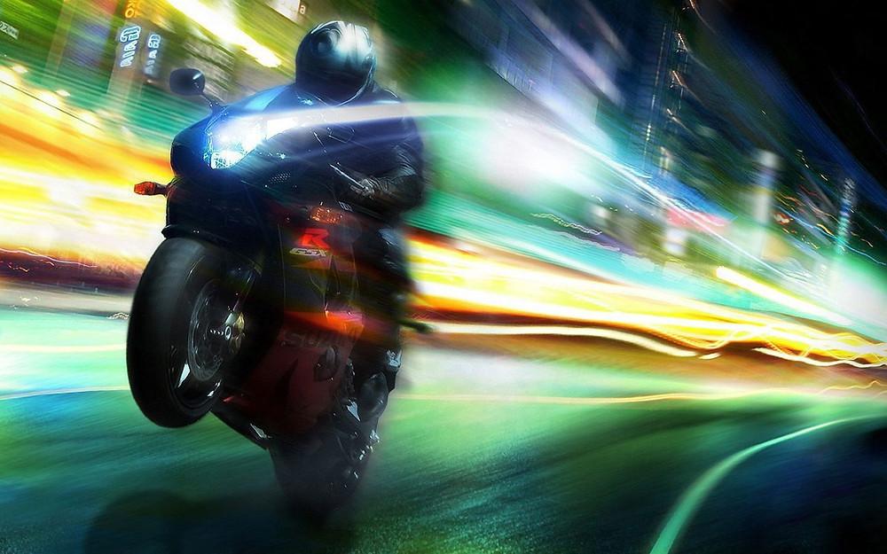 בפוקוס עלתמונת לילה עם אורות מרוחים ממהירות, אופנוע מרים גלגל על רקע מרוח.