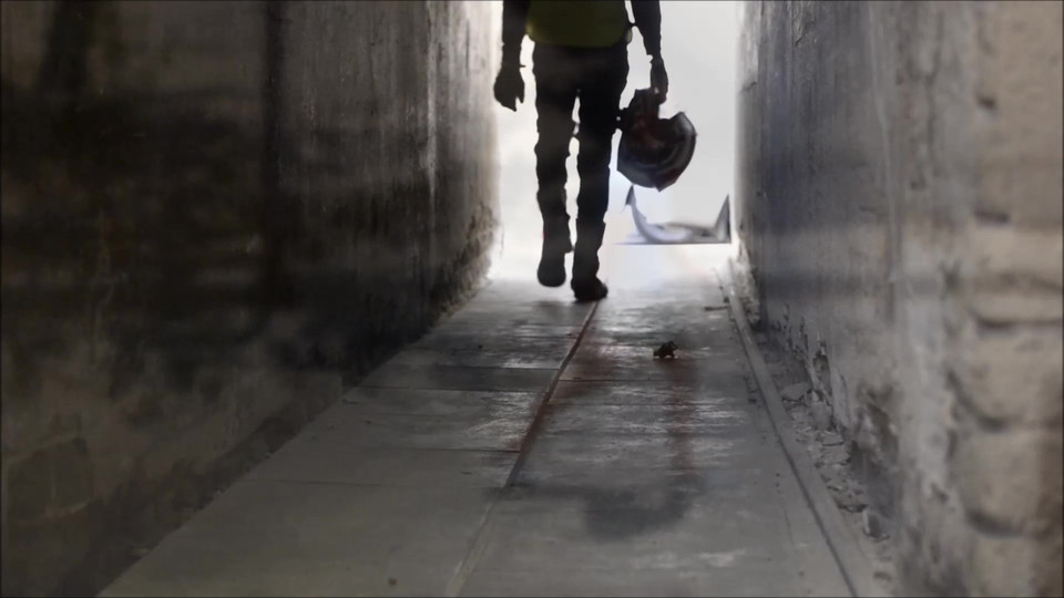 צללית של אדם הולך עם קסדה ביד במזדרון חשוך שבקצה אור
