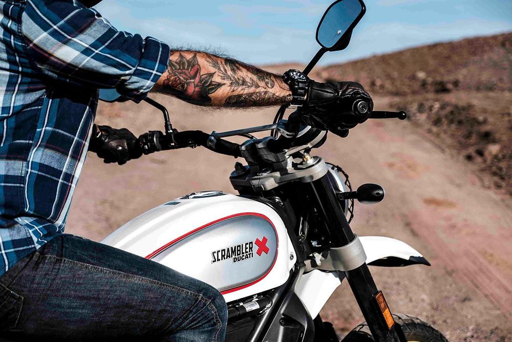 תמונת תקריב של אדם עם יד מקועקעת על אופנוע דוקאטי סקרמבלר לבן ברקע שביל ונוף חום