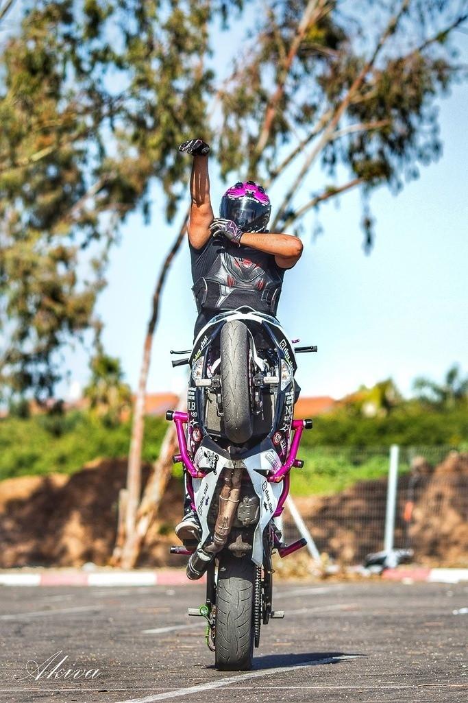 אופנוע סטאנט בווילי, רוכב בעמידה בלי ידיים בתנועת זריקה של כדור, מגרש אספלט, עצים