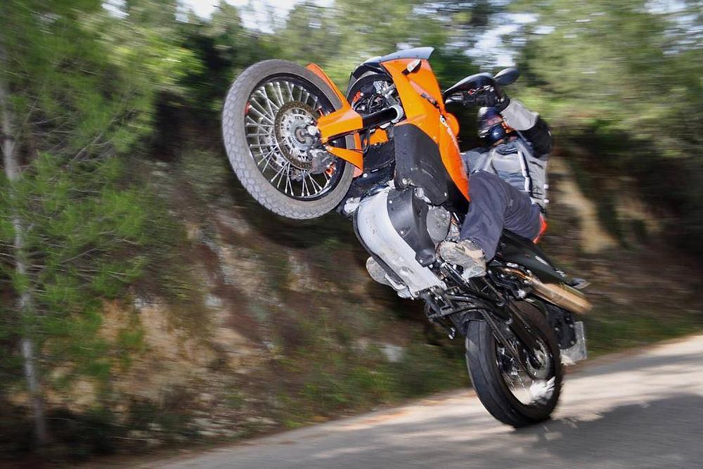 אופנוע אדוונצ'ר כתום של קטמ בווילי על כביש בתוך עצים