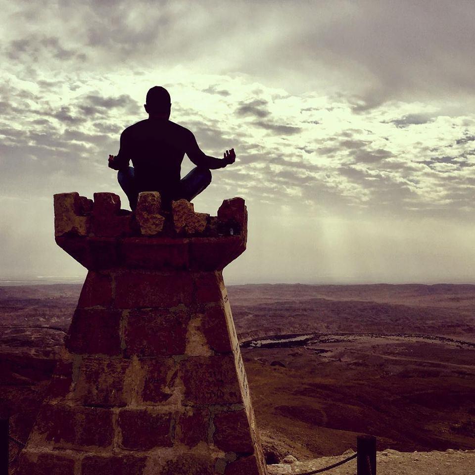 איש עושה מדיטציה על צריל ברקע שמיים ומדבר