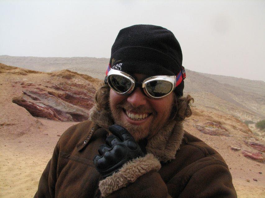 תמונת תקריב של אדם ברקע מדבר, חובש משקפי אבק, כובע גרב ומחזיק את הסנטר מבעד לכפפה